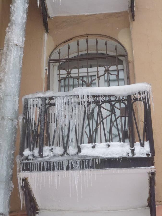 Сцена города зимы с сосульками на здании Faccade дома, балкон стоковые изображения