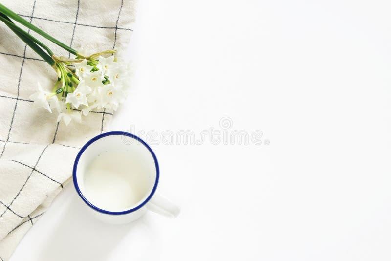 Сцена завтрака с кружкой молока, полотенца для чайной посуды и букета narcissus, daffodil цветет на белой предпосылке таблицы Вес стоковое фото rf