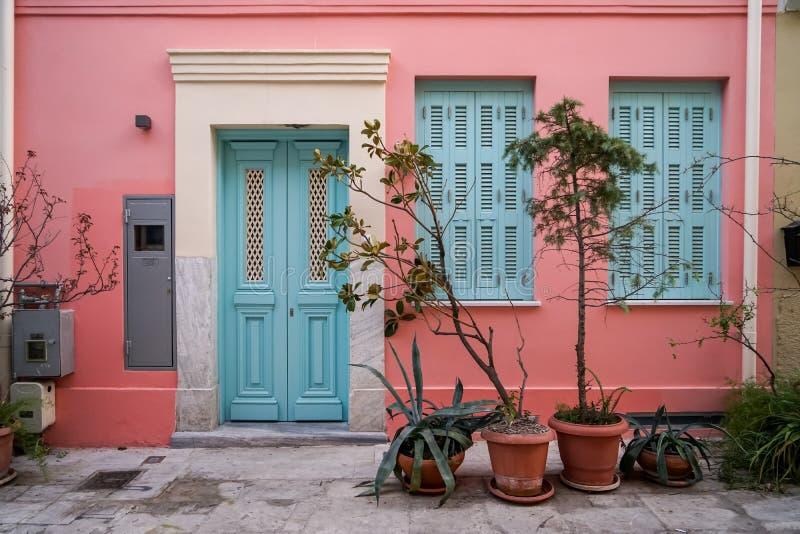 Сцена красивой городской предпосылки фасада здания в стене краски гипсолита пастельного пинка, свете - голубая дверь входа и окна стоковая фотография