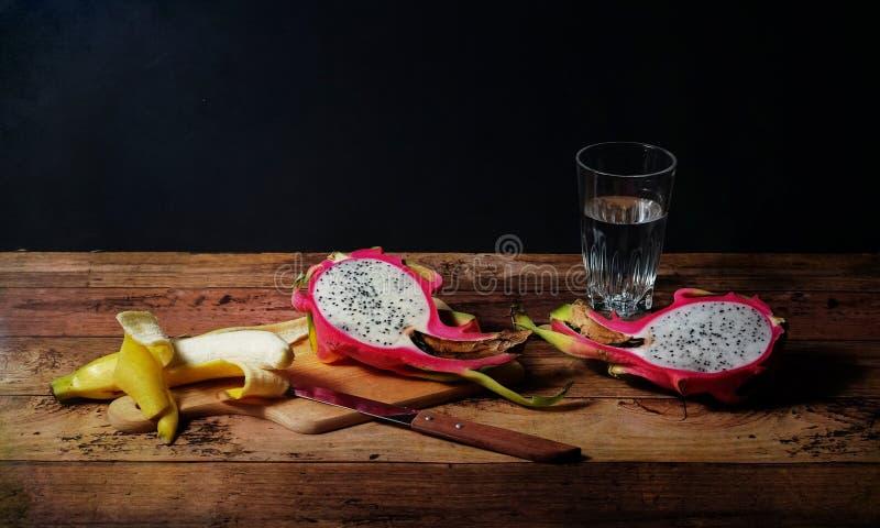 Сцена плодоовощ плодоовощ и банана дракона на деревянном столе в темной предпосылке стоковые фотографии rf