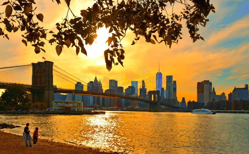 Сцена пляжа с молодыми людьми смотря Гудзон и красочный теплый оранжевый заход солнца на горизонте архитектуры Манхэттена совреме стоковое изображение