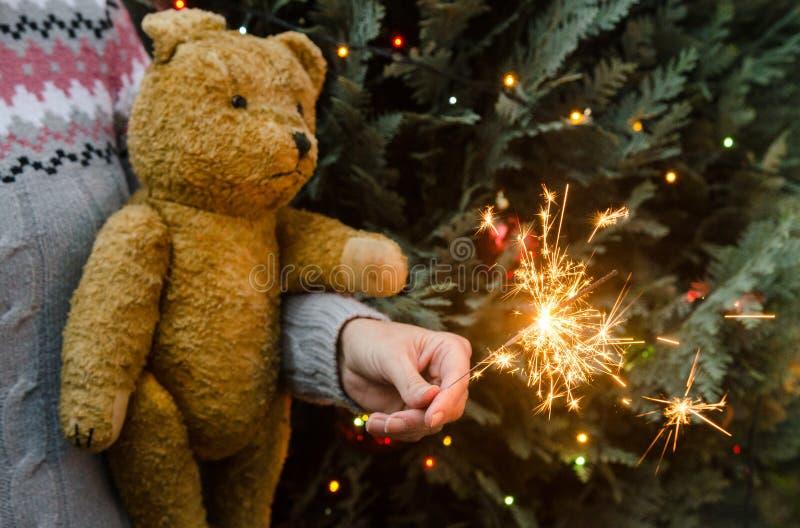Сцена рождества - плюшевый мишка и бенгальский огонь удерживания женщины перед рождественской елкой стоковое изображение