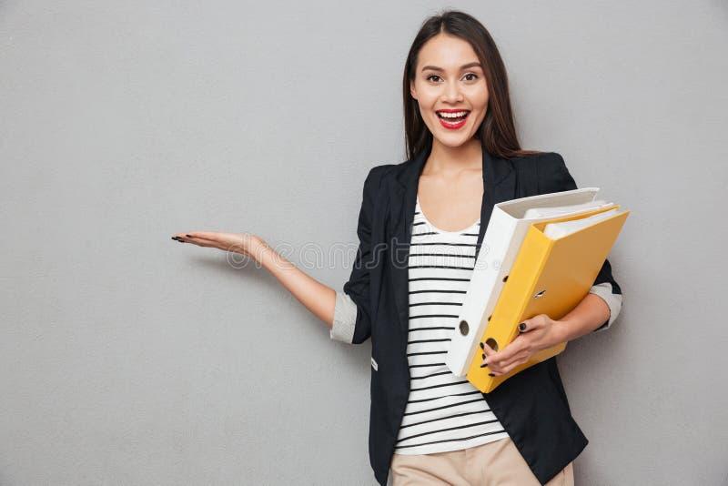 Счастливая азиатская бизнес-леди при папки держа copyspace на ладони стоковое фото rf