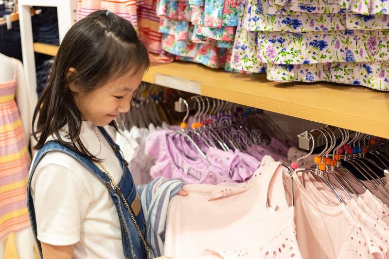 Счастливая азиатская девушка выбирает одежды в моле или магазине одежды, s стоковое изображение