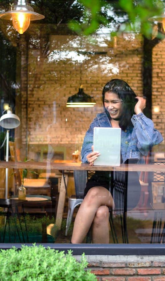 Счастливая азиатская женщина используя планшет в кафе стоковая фотография