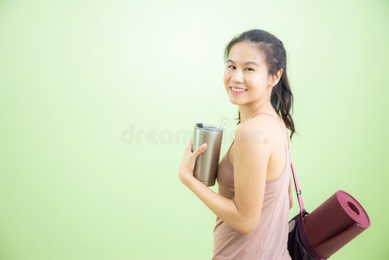 Счастливая азиатская женщина пойти к студии йоги стоковые фотографии rf