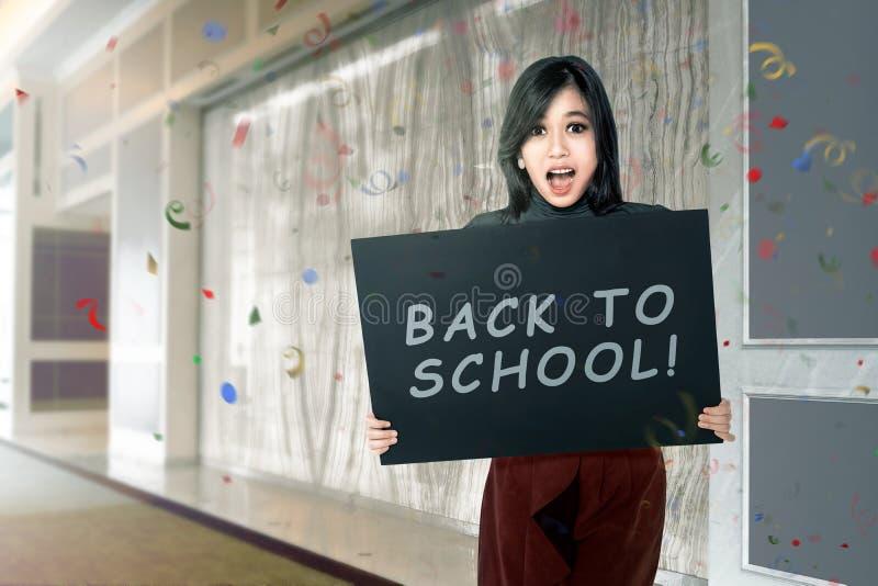 Счастливая азиатская женщина студента с доской с назад к тексту школы стоковое фото