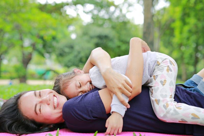 Счастливая азиатская мама обнять ее дочь лежа в зеленой лужайке Смешная девушка матери и ребенка играя в парке лета стоковая фотография rf