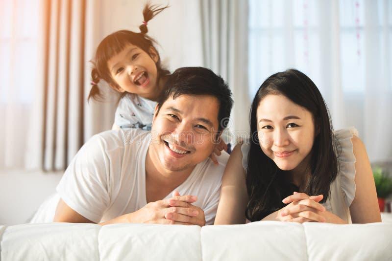 Счастливая азиатская мать отца семьи при дочь смотря wi камеры стоковые фотографии rf