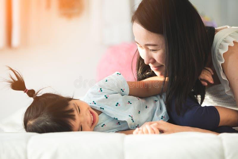 Счастливая азиатская мать семьи при дочь играя на кровати с smil стоковые изображения