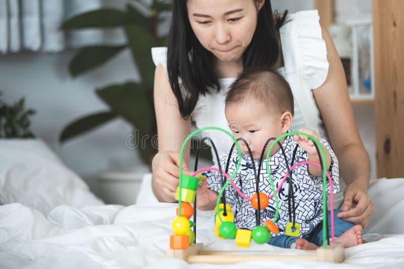 Счастливая азиатская мать семьи при младенец сына играя на кровати с smil стоковое изображение rf