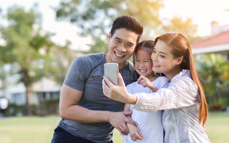 Счастливая азиатская семья принимая selfie со смартфоном совместно стоковая фотография