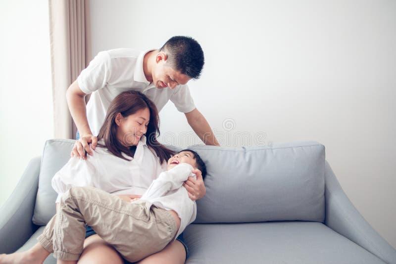 Счастливая азиатская семья с сыном дома на софе играя и смеясь стоковые фотографии rf