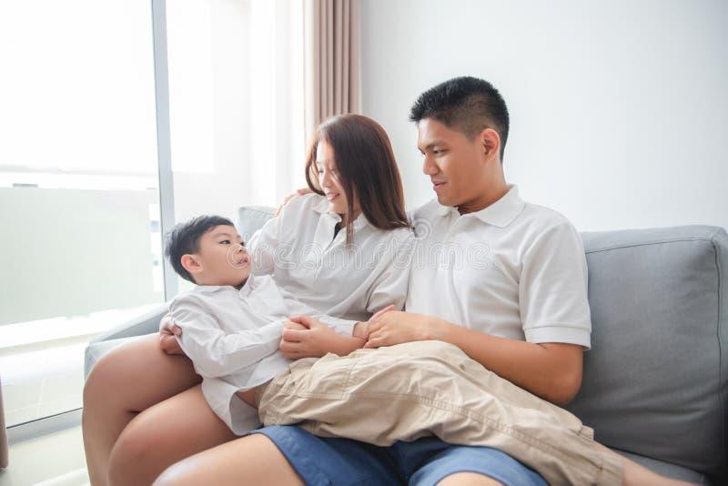 Счастливая азиатская семья с сыном дома на софе играя и смеясь стоковые фото