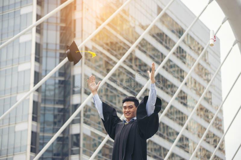 счастливая азиатская студентка, получившая диплом и степень магистра в колледже, в академической одежде и шапке Студент и выпускн стоковая фотография