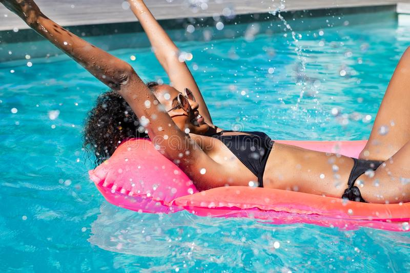 Счастливая африканская женщина брызгая воду в бассейне стоковая фотография