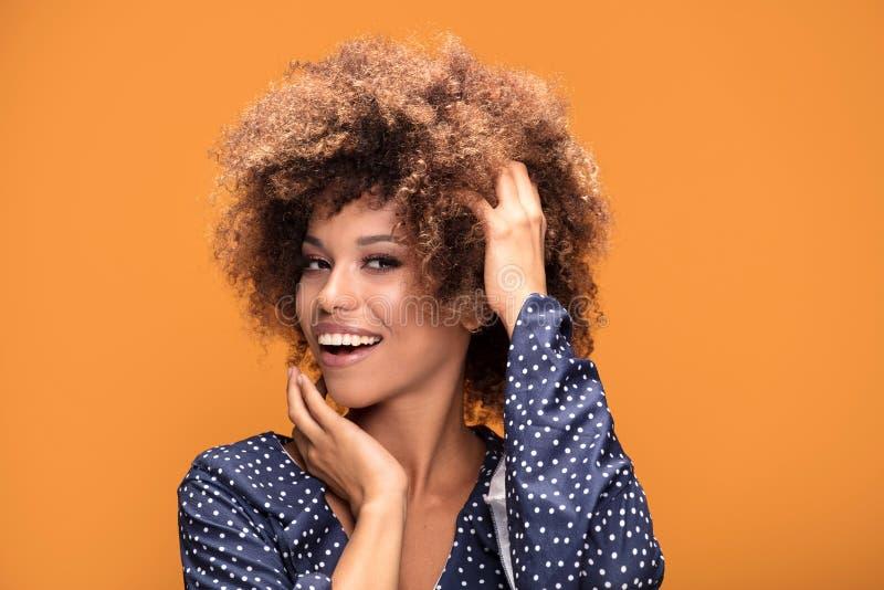 Счастливая Афро-американская дама усмехаясь на желтой предпосылке стоковые изображения rf