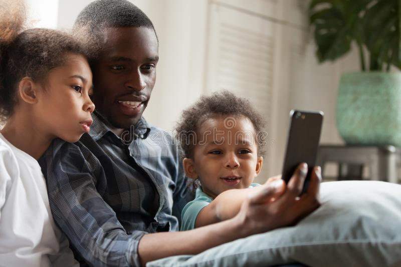 Счастливая Афро-американская семья используя мобильный телефон совместно стоковая фотография rf
