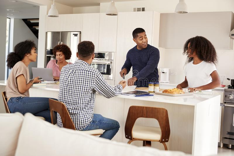 Счастливая Афро-американская семья на их острове кухни, говоря и подготавливая семейную трапезу совместно стоковые фотографии rf