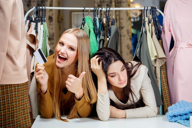 Счастливая белокурая девушка делая покупки с кредитной карточкой, а ее друг не имеют кредитную карточку и унылый стоковые изображения