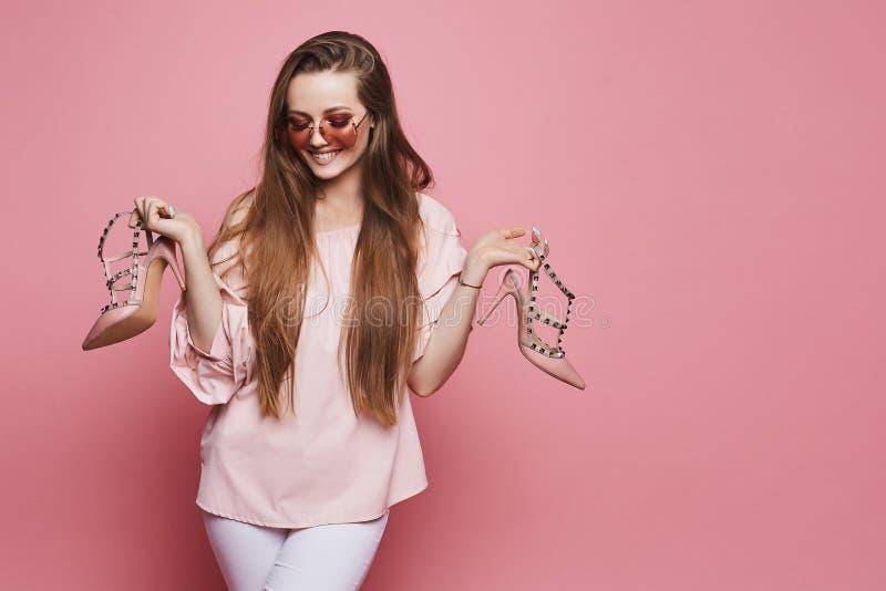 Счастливая белокурая модельная девушка с сияющей улыбкой в бежевой блузке и в модных розовых солнечных очках держа стильные ботин стоковые фото