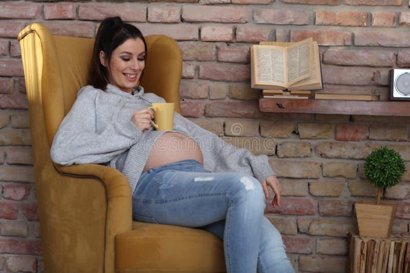 Счастливая беременная женщина дома ослабляя в кресле стоковые фотографии rf