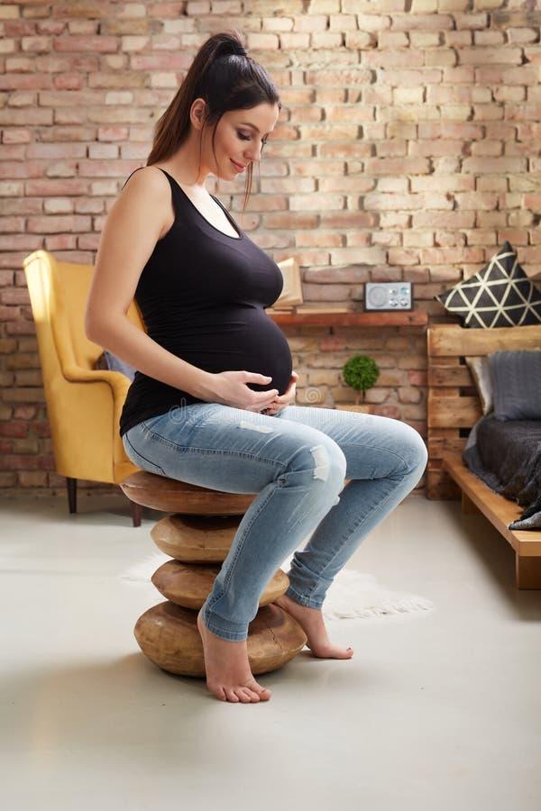 Счастливая беременная женщина сидя дома стоковые изображения
