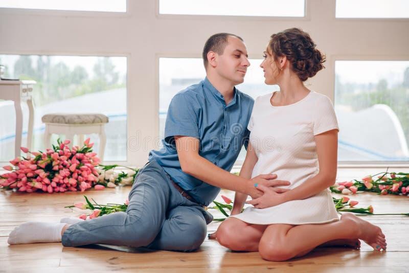 Счастливая беременная женщина с ее супругом держащ и слушающ к младенцу в животе и устанавливающ на пол ` s живущей комнаты на стоковое изображение