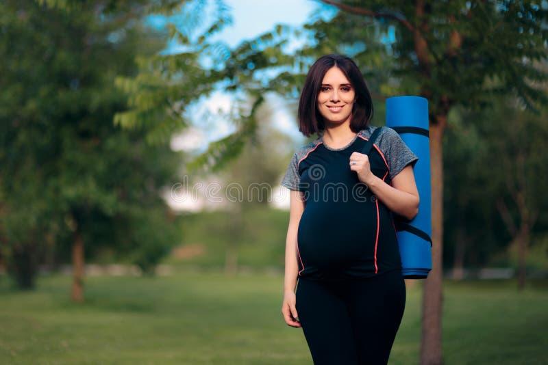 Счастливая беременная женщина с Outdoors циновки йоги стоковые фотографии rf