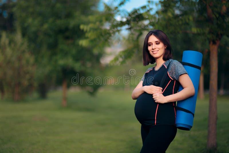 Счастливая беременная женщина с Outdoors циновки йоги стоковая фотография