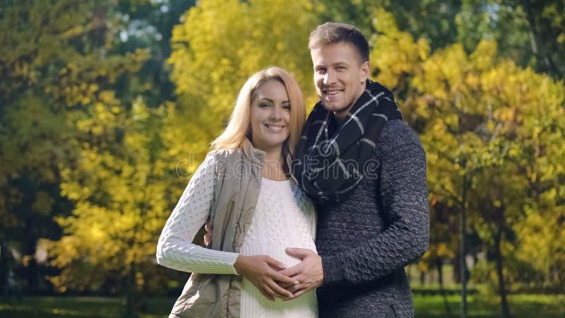 Счастливая беременные дама и супруг штрихуя живот и смотря камеру, родителей стоковое изображение