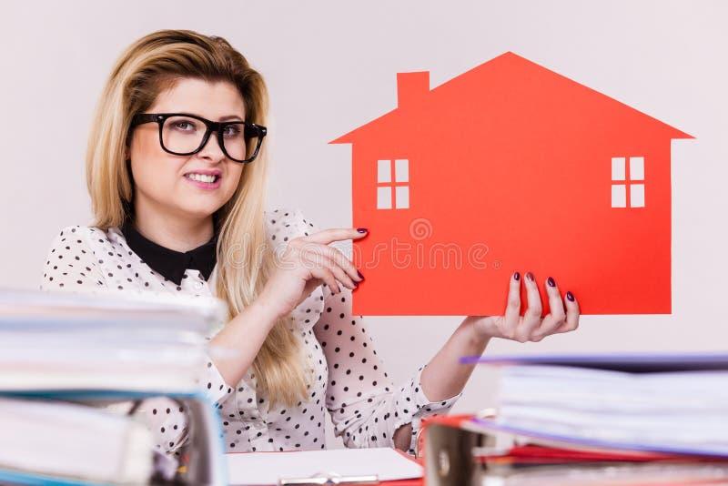 Счастливая бизнес-леди в офисе держа дом стоковые изображения rf