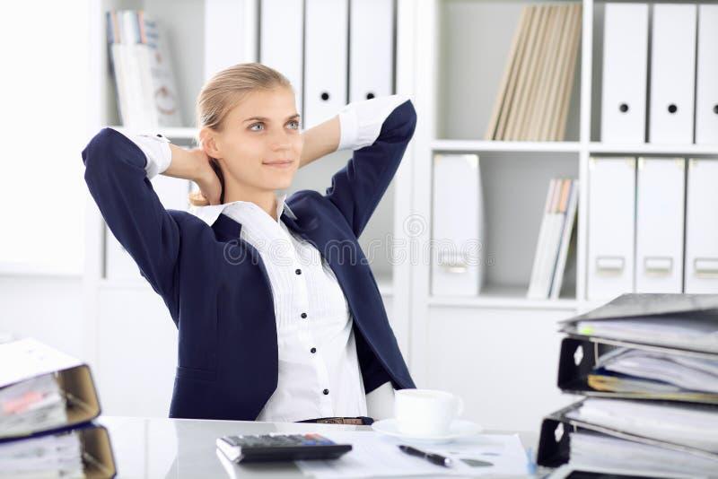Счастливая бизнес-леди или женский бухгалтер имея некоторые минуты для времени с и удовольствия на месте службы E стоковые изображения