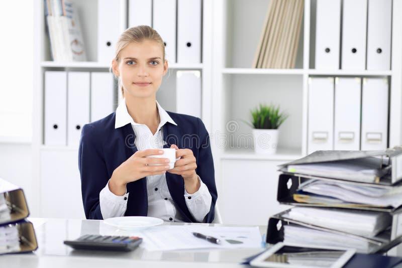 Счастливая бизнес-леди или женский бухгалтер имея некоторые минуты для времени с и удовольствия на месте службы E стоковое изображение