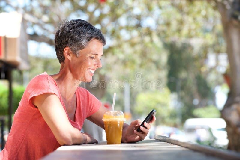 Счастливая более старая женщина сидя снаружи с мобильным телефоном и питьем стоковая фотография