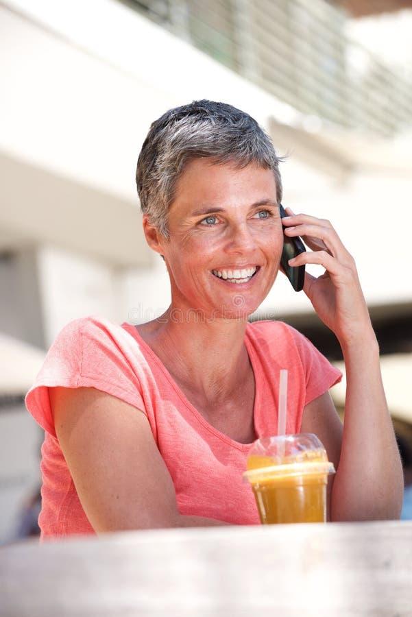 Счастливая более старая женщина сидя снаружи с питьем и говоря на мобильном телефоне стоковая фотография rf