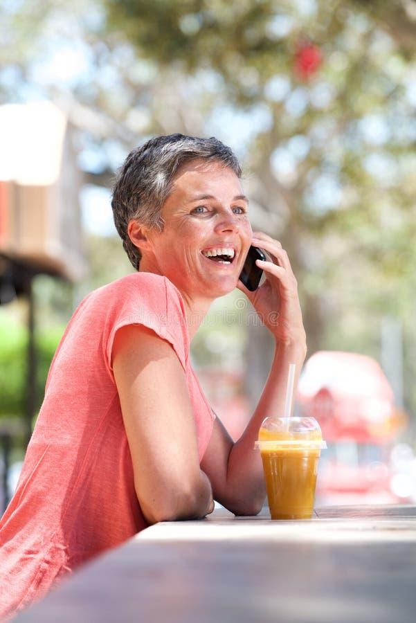 Счастливая более старая женщина сидя снаружи с питьем и говоря на телефоне стоковые фотографии rf