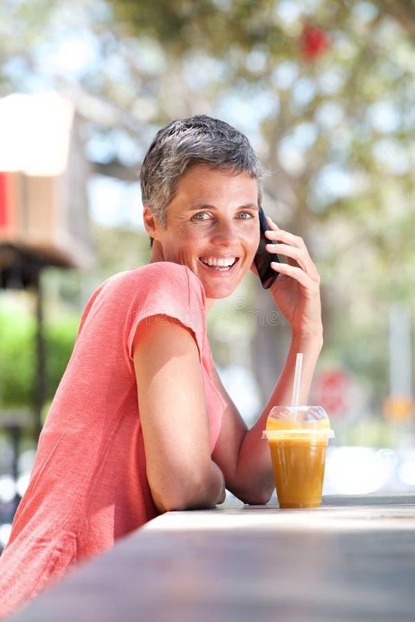 Счастливая более старая женщина сидя снаружи с питьем и говоря на мобильном телефоне стоковое фото