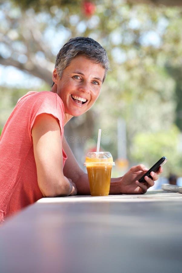 Счастливая более старая женщина сидя снаружи с питьем и используя мобильный телефон стоковое фото