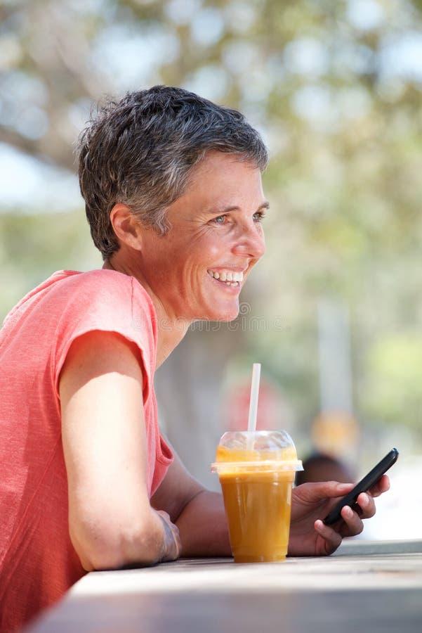 Счастливая более старая женщина сидя снаружи с питьем и используя сотовый телефон стоковые изображения