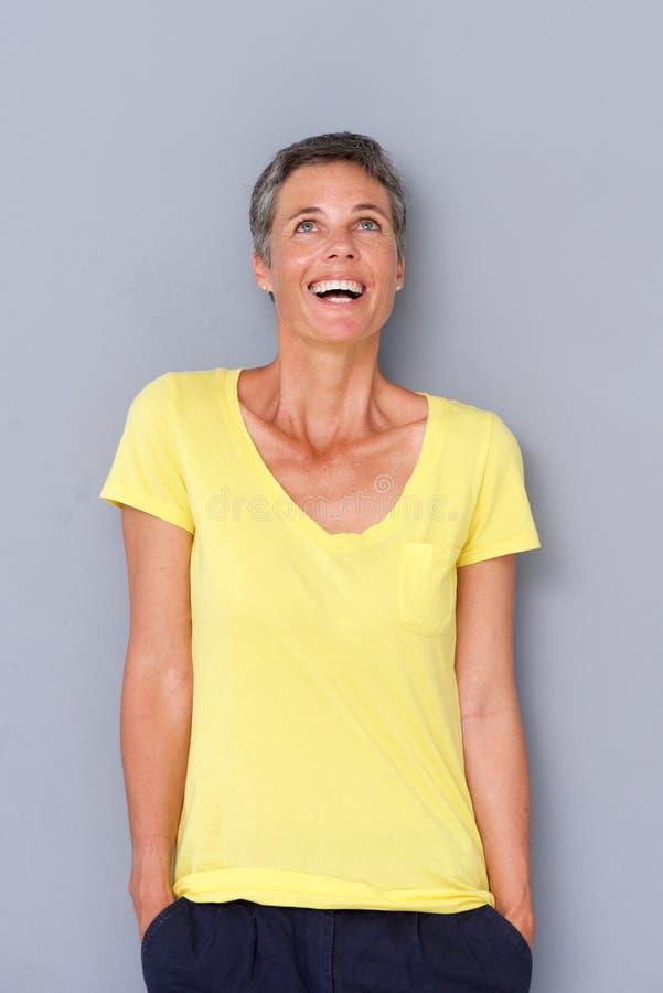 Счастливая более старая женщина смеясь над серой стеной стоковое фото rf