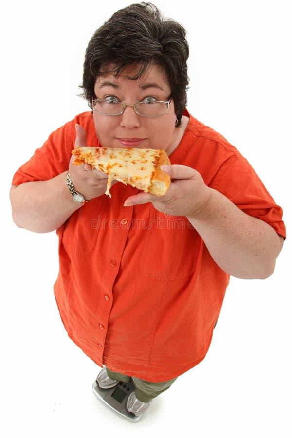 Счастливая брюзглая женщина на маштабе с пиццей стоковые фотографии rf