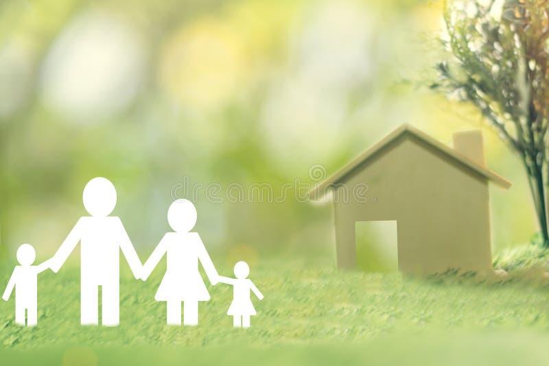 Счастливая бумага семьи на зеленой траве видит дом для сохраняя продажи денег стоковые фотографии rf