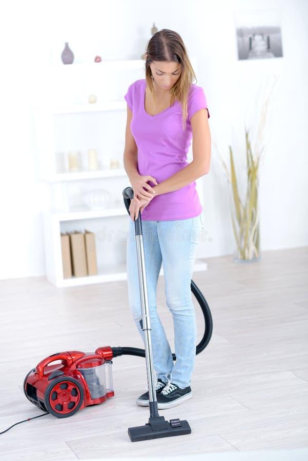 Счастливая взрослая белокурая девушка hoovering в живущей комнате и усмехаться стоковое фото rf