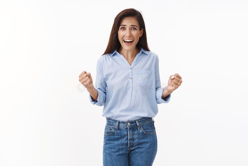 счастливая счастливая счастливая взрослая женщина говорит хурай, празднующая победа, кулак, победа кулака, улыбка в широком пасе  стоковая фотография