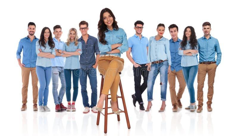 Счастливая вскользь команда при их руководитель женщины сидя на стуле стоковое изображение