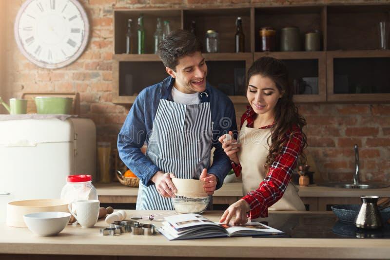 Счастливая выпечка молодой женщины и человека в кухне просторной квартиры стоковая фотография rf