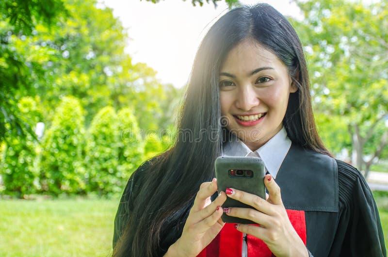Счастливая градуированная молодая женщина в мантии разговаривая с родителем в мобильном телефоне и смотря камеру с предпосылкой п стоковые фотографии rf