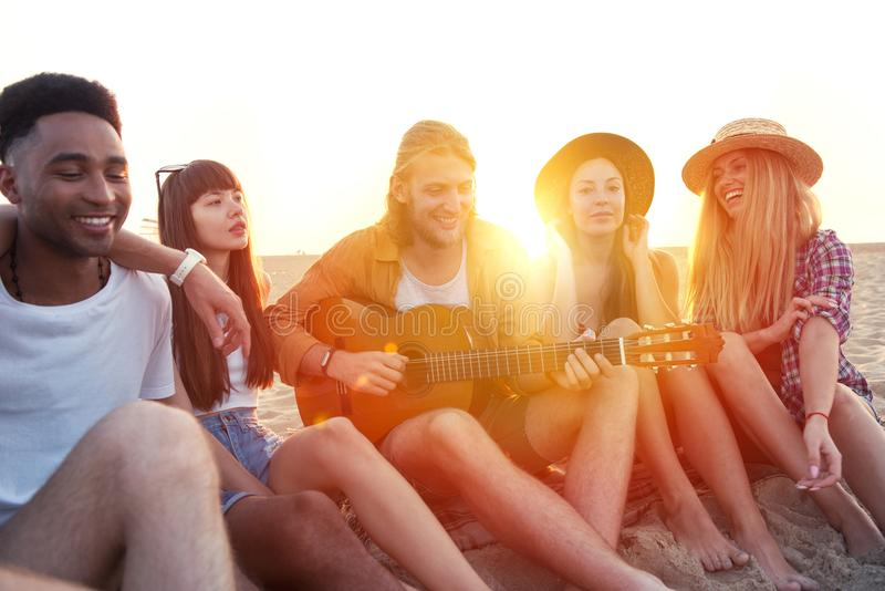 Счастливая группа в составе друг имея партию на пляже стоковое изображение rf