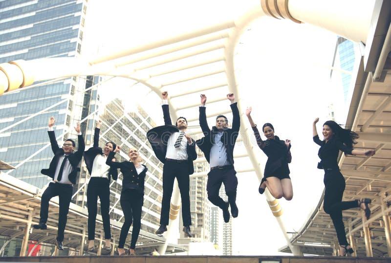 Счастливая группа сыгранности дела скачет вверх Торжество концепции стоковое фото